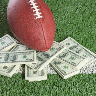 football and money on football field