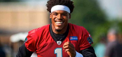Cam Newton running towards the camera with a huge smile